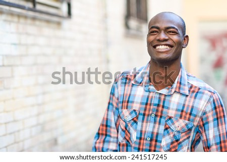 Portrait of black man very happy, smiling in urban background - stock photo