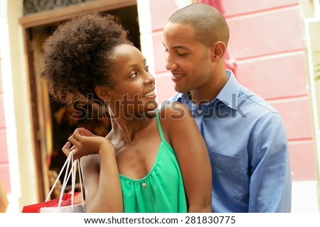 Portrait of black tourist heterosexual couple in Casco Antiguo - Panama City with shopping bags. The man and his girlfriend smile at each other - stock photo