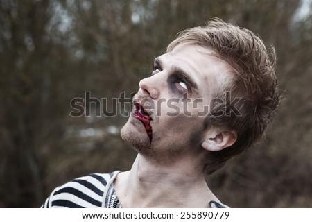 Portrait of bleeding man with zombie makeup - stock photo