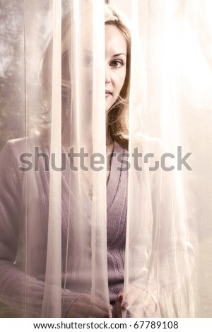 Portrait of blond and attractive woman standing next to the window behind the curtains. Silhouette of beautiful woman with brown eyes.