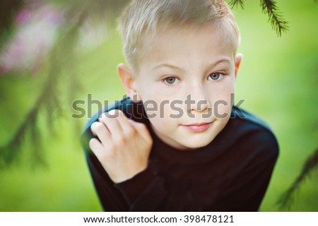 Portrait of blond boy with freckles, close-up, face framed by pine branches. - stock photo
