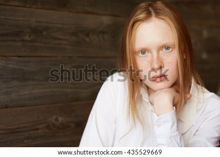 Portrait of blond Caucasian girl with blue eyes and ivory skin. Young female model in white official shirt sitting and looking at camera with her chin on her arm. Simple and beauty concept. - stock photo