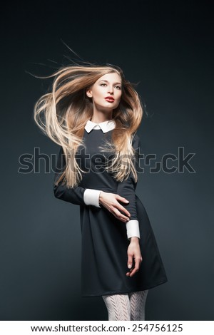 Portrait of blond fashion model posing with hair fluttering in the wind and touching her arm. - stock photo