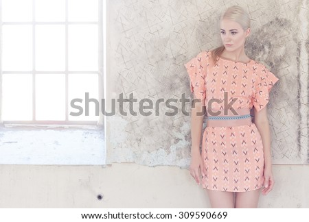 Portrait of blond female in pink dress over grey wall. - stock photo