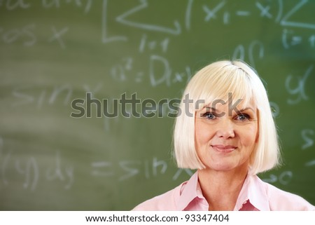 Portrait of blond female looking at camera with blackboard on background - stock photo