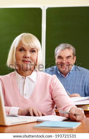 Portrait of blond female looking at camera with senior man on background - stock photo
