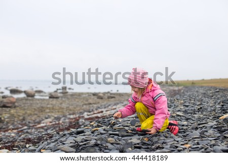 portrait of blond girl in preschool age sitting down with sea coast with small stones and rocks in south sweden on cloudy day and playing  - stock photo