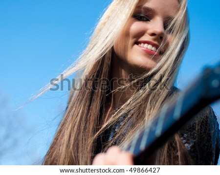 Portrait of blond girl playing a guitar outdoors