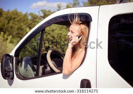 Portrait of blond girl speaking phone and looking from car window. Young woman excited and smiling while talking with someone on sunny countryside background.