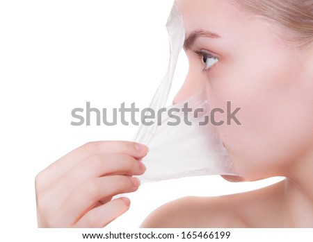 Portrait of blond girl young woman in facial peel off mask. Peeling. Beauty and body skin care. Isolated on white background. Studio shot. - stock photo