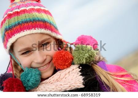 Portrait of blond little girl wearing wool cap - stock photo