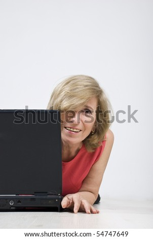 Portrait of blond mature woman hidden half behind laptop smiling for you,copy space for text message in right part of image