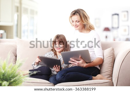 Portrait of blond mother and her cute daughter sitting at home in living room and both of them using digital tablet.