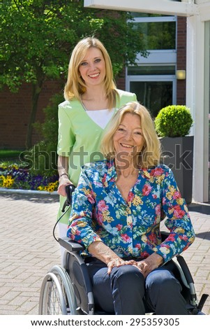 Portrait of Blond Nurse Pushing Senior Woman in Wheelchair in front of Building Entrance on Sunny Day. - stock photo
