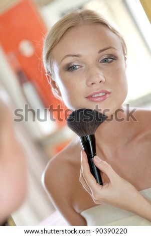 Portrait of blond woman applying powder on her face - stock photo