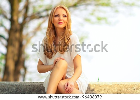 portrait of blond woman in white dress outdoor - stock photo