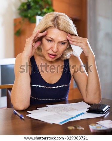 Portrait of blond woman reading utility payments at the table in home or office