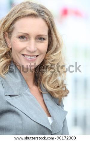 Portrait of blond woman turning head towards camera - stock photo