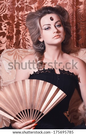 Portrait of blond woman with a fan - stock photo