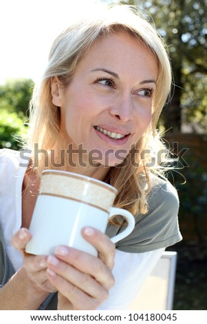 Portrait of blond woman with tea mug sitting outside - stock photo