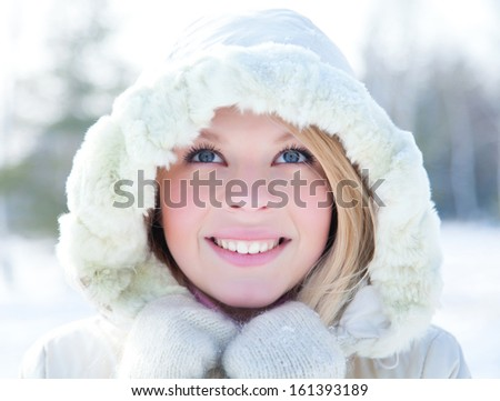 Portrait of blond young woman in fur coat at winter background - stock photo