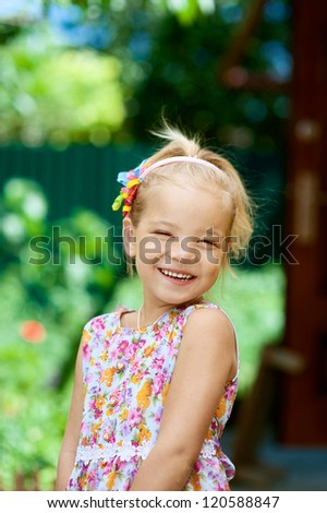 Portrait of blonde beautiful smiling little girl close-up, against background of summer park.