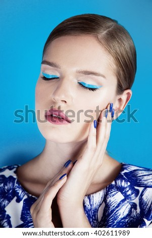 Portrait of blonde beautiful young woman with evening makeup and pink lipstick, blue background.  - stock photo