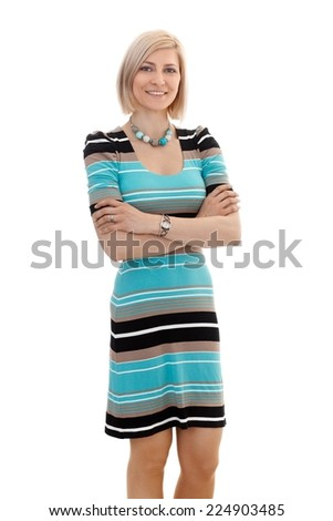 Portrait of blonde businesswoman in casual clothing standing with arms crossed, looking at camera, white background. - stock photo
