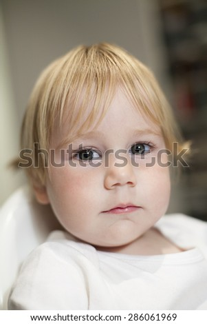 portrait of blonde caucasian baby nineteen month age chubby face looking at camera with serious expression - stock photo