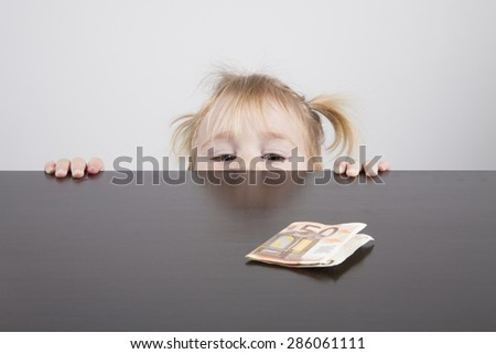 portrait of blonde caucasian baby nineteen month age with pigtails chubby face  looking at Euro banknote on brown table horizontal - stock photo
