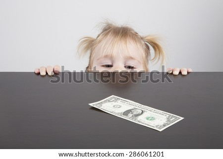 portrait of blonde caucasian baby nineteen month age with pigtails chubby face yellow shirt looking at dollar banknote on brown table horizontal - stock photo