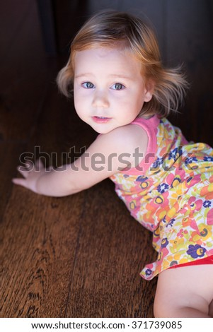 portrait of blonde caucasian baby two years old chubby face looking at camera with pretty expression and beautiful eyes wearing a flower colorful dress or summer shirt lying on wood floor - stock photo