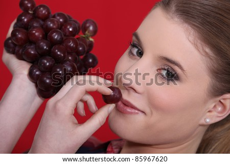 portrait of blonde eating red grapes - stock photo