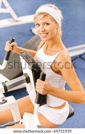 portrait of blonde girl exercising in gym on various machines