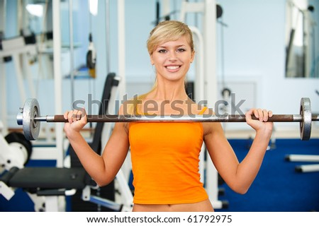 portrait of blonde girl exercising in gym with weight - stock photo
