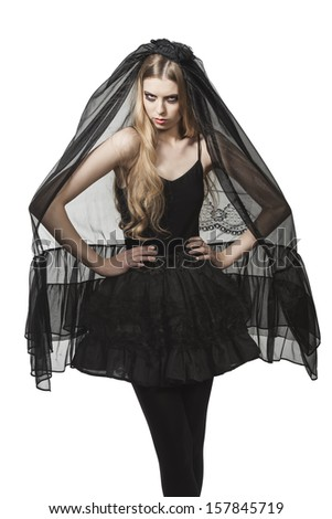 portrait of blonde girl with Halloween costume, funeral style and creative make-up wearing long dark veil and bizarre skirt - stock photo