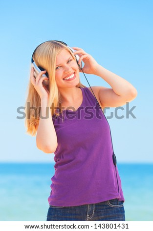 Portrait of blonde girl with headphone on the beach. - stock photo