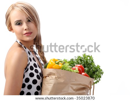 Portrait of blonde holding bag paper sack in hands full of  fruits and vegetables