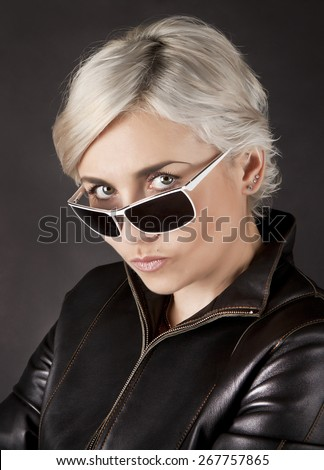 Portrait of blonde in dark glasses and leather jacket - stock photo
