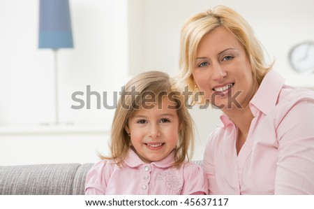 Portrait of blonde little girl and mother wearing pink, smiling.