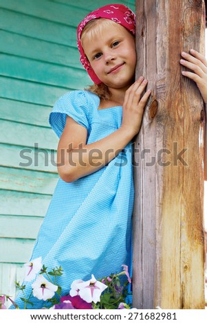 Portrait of blonde little girl standing in the garden next to the flowers. - stock photo