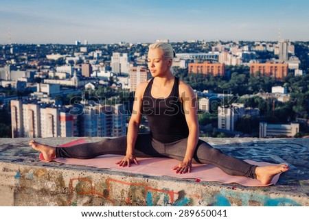 Portrait of blonde strong woman in sportwear doing workout split on the roof of a skyscraper above the big city at early morning. Female sporty muscular body. Dawn and sunrise bright sunny light.  - stock photo