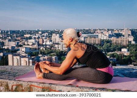 Portrait of blonde strong woman in sportwear doing workout stretching on the roof of skyscraper above the big city at early morning. Female sporty and sexy muscular body. Fitness concept.