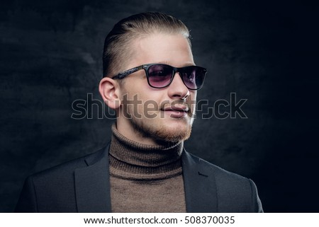 Portrait of blonde, stylish male in sunglasses in turtle-neck sweater on dark grey background.