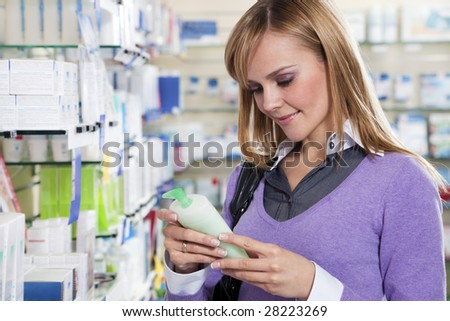 Portrait of blonde woman reading label of shampoo in pharmacy. Copy space - stock photo