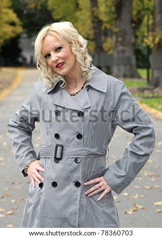 portrait of blonde woman walking in park