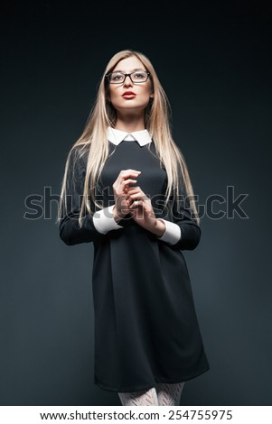 portrait of blonde young beautiful posing woman wearing eyeglasses and black dress with white collar. Her hands together. - stock photo