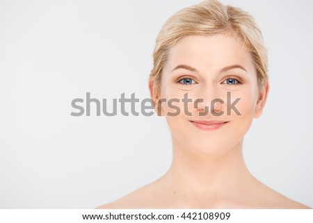 Portrait of blonde young pretty girl smiling, looking at camera, over white background.