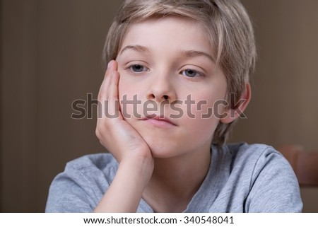 Portrait of blonde young sad boy thinking - stock photo