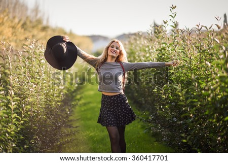 Portrait of blonde young woman happy with open arms in rural road. Girl wearing sweater, skirt and hat
